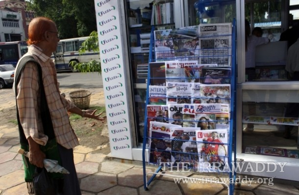 A Rangoon man looks at daily newspapers and journals at a newsstand. (PHOTO: Irrawaddy)