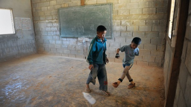 Youngsters in remote Shan State kick a water bottle around a barren classroom. (Photo: Steve Tickner)