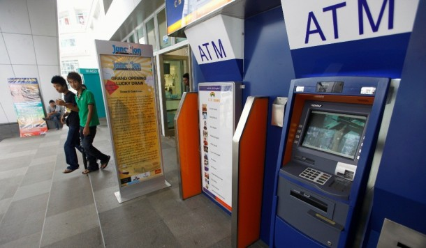 People walk past ATM machines at a shopping centre in Rangoon May 27, 2012. Private banks in Burma have begun rolling out automated teller machines in recent weeks, revolutionary in a country where people often haul sacks and suitcases of cash to banks. (Photo: Reuters / Soe Zeya Tun)