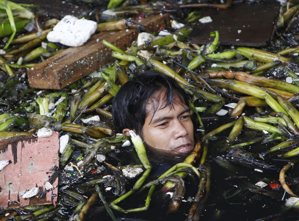 man wades on neck deep murky waters to salvage materials from