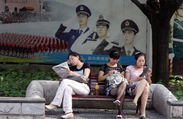 Women sit on a bench in front of a poster depicting Chinese soldiers in Beijing on July 13. (PHOTO: Reuters)