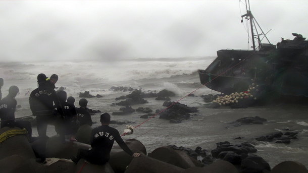 Police try to rescue crew members of a stranded Chinese fishing boat on Jeju Island on Tuesday. (Photo: Reuters)