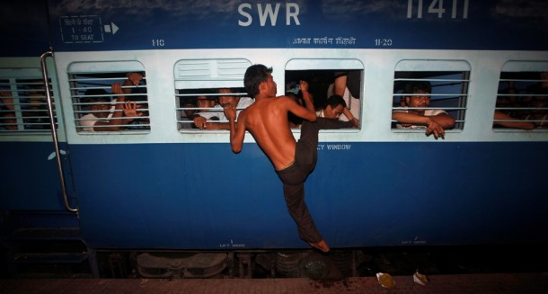 A man from India's northeastern Assam State tries to board an overcrowded train through a window before it leaves Calcutta Railway Station. (Photo: Reuters)