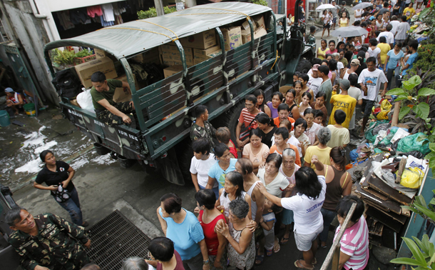 Residents queue for relief goods on Monday after their shanties were submerged by floodwaters in Santa Mesa, Metro Manila. (Photo: Reuters)