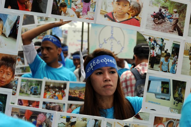 A protester holds a large collage of photos relating to the Kachin State conflict. (Photo: Steve Tickner / The Irrawaddy)