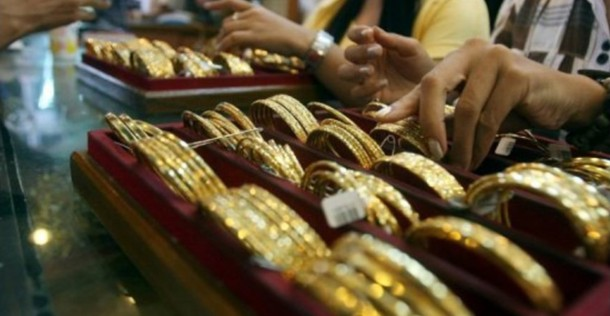 Vendors arrange a display of gold jewelry at a shop in Chinatown in downtown Rangoon.