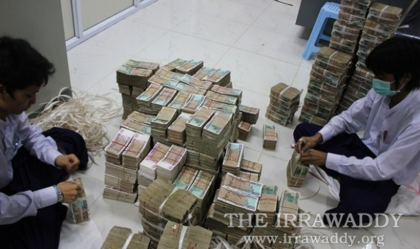 Burmese kyat currency being counted in Rangoon. (Photo: Jpaing / The Irrawaddy)