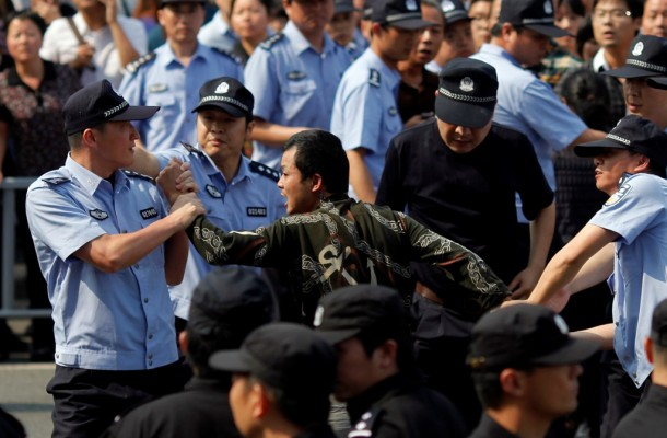 Police officers arrest a protester during a protest on Saturday against plans to expand a petrochemical plant in Ningbo, Zhejiang Province. (Photo: Reuters)