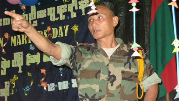 Standing beneath Martyrs Day decorations at a jungle base in KNLA Brigade 5 in 2009, Brig-Gen Baw Kyaw Heh addresses an audience. (PHOTO: Saw Yan Naing/ THE IRRAWADDY)