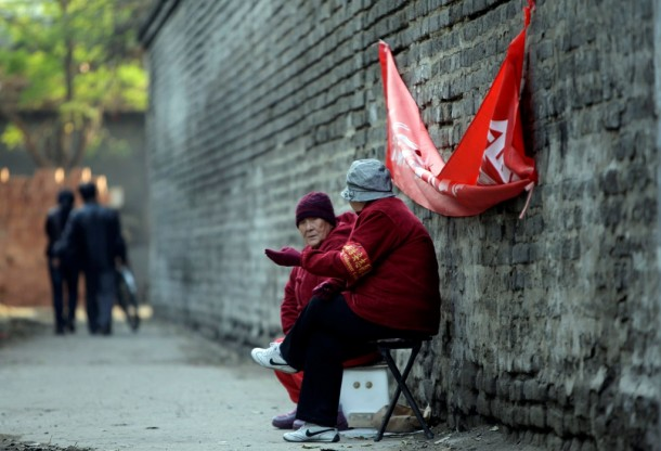 Local elderly security volunteers with red armbands chat as they sit to watch over an alleyway in central Beijing. (Photo: Reuters)