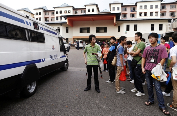 A police van reverses out of the premises of a dormitory as negotiations with striking bus drivers continue within the building in Singapore. (Photo: Reuters)