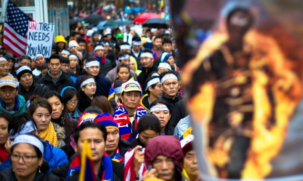 Protesters stand behind photo of victim of self-immolation during solidarity march in support of Tibet in New York. (Photo: Reuters)