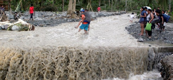Residents cross a flooded road which was destroyed after Typhoon Bopha hit Compostela Valley. (Photo: Reuters)