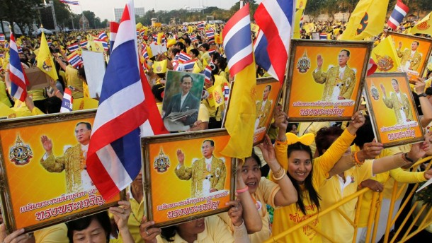 People hold pictures of Thailand's King Bhumibol Adulyadej as they wait for him to arrive at the Anantasamakom Throne Hall in Bangkok. (Photo: Reuters)