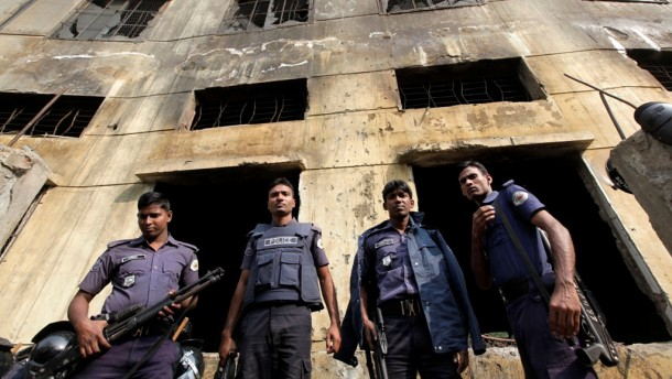 Police officers gather in front of the burnt building of garment factory Tazreen Fashions in Savar, Bangladesh. (Photo: Reuters)