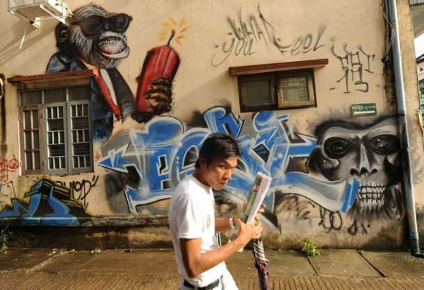 A man walks past a wall covered with grafitti in a Rangoon neighborhood. (Photo: Steve Tickner / The Irrawaddy)