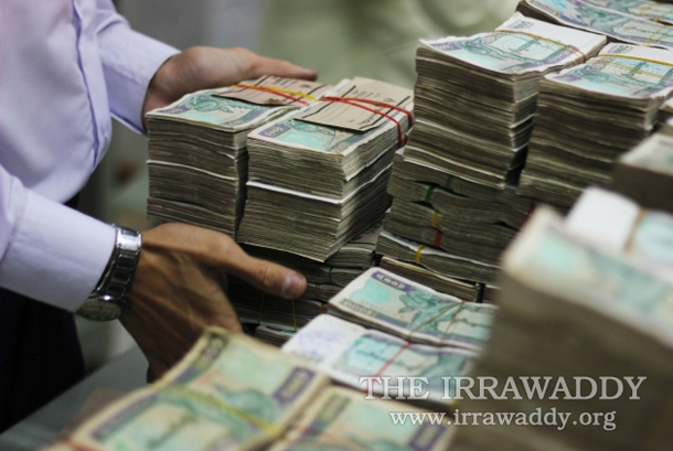 Piles of Burmese kyat currency are counted in Rangoon. (Photo: Jpaing / The Irrawaddy)