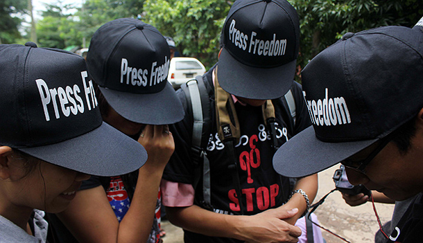 Journalists in black caps and T-shirts gather outside the courtroom in Dagon Township where the Voice Weekly journal was facing charges of defaming the Ministry of Mines in August. (Photo: Jpaing / The Irrawaddy)