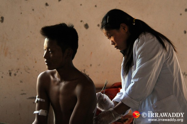 A young Kachin soldier is treated for shrapnel injuries at the Laiza Military Hospital. (Photo: Steve Tickner / The Irrawaddy)