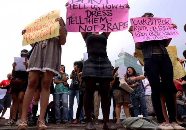 Women wearing miniskirts and tight leggings hold posters to protest against the idea that provocatively dressed women are to blame for sexual assaults, in Jakarta on Sept. 18, 2011.