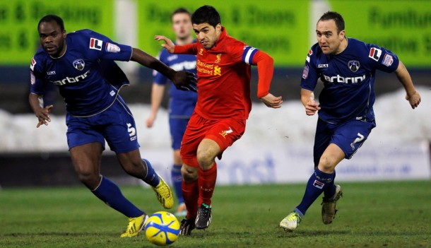 Liverpool's Luis Suarez, center, is challenged by Oldham Athletic's Jean-Yves M'Voto, left, and Lee Croft during their FA Cup fourth round soccer match at Boundary Park in Oldham, northern England, on Jan. 27, 2013. (Photo: Reuters)