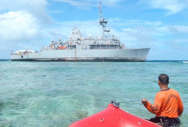A member of the Philippine Coast Guard approaches the USS Guardian, which ran aground on the Tubbataha Reef, a UNESCO World Heritage Site, on Jan. 17. (Photo: Reuters)