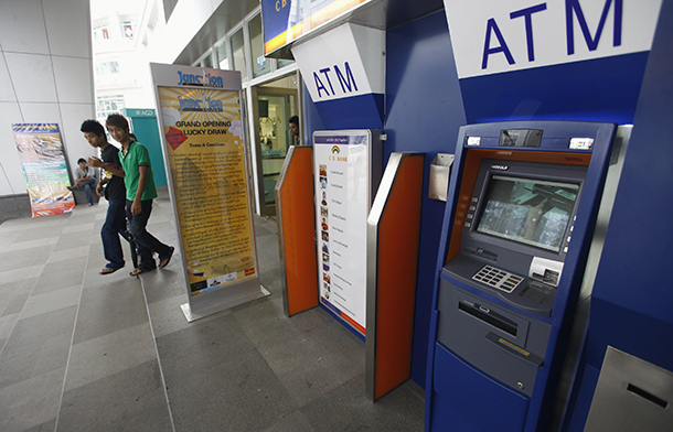 People walk past ATMs at a shopping center in Rangoon in May 2012. (Photo: Reuters)