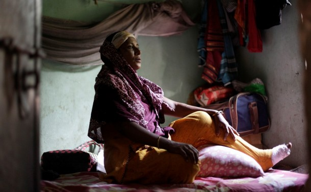 Ale Noor, 35, who survived a devastating fire at the Tazreen Fashions garment factory on Nov. 24, sits inside her slum room. (Photo: Reuters)