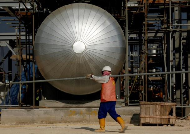 A worker carries a pipe as he walks near a storage tank at Banyu Urip well on the Exxon Mobil site in Cepu, Indonesia's Central Java Province, on July 15, 2009.