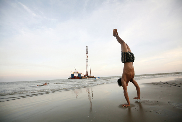 A boy exercises on a beach as ships involved in the construction of the Yadana underwater gas pipeline project in southern Burma are moored in the background. (Photo: Reuters)