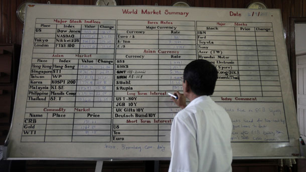 A worker at the Myanmar Securities Exchange Center writes on a white board in September 2011. Despite reforms, Burma still faces hurdles in attracting foreign investors. (Photo: Reuters)