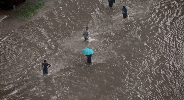 People walk on a flooded street in Jakarta on Jan. 17, 2013. Heavy monsoon rains in western Indonesia triggered landslides that killed at least 16 people on Jan. 27. (Photo: Reuters)