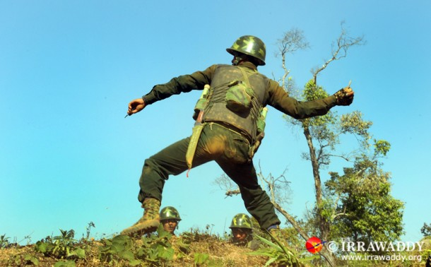 A KIA soldier lobs a grenade at Burmese army forces advancing on Hkaya Bum on Sunday. (Photo: Steve Tickner / The Irrawaddy)