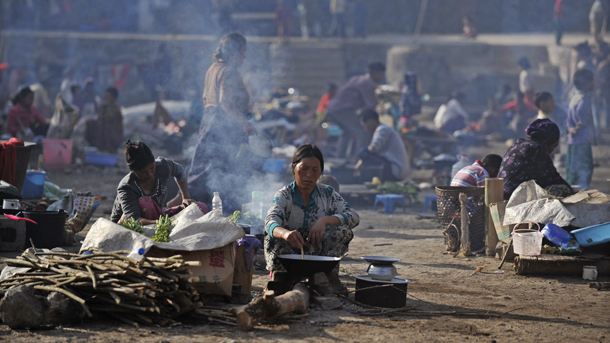 Refugees from Kachin State cook meals at a temporary camp by the Chinese border in May last year. (Photo: Reuters)