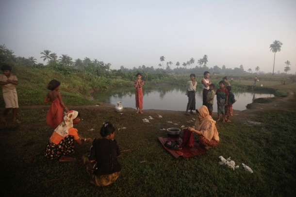 People displaced by violence in Arakan State, western Burma, wash clothes by a pond near Owntaw refugee camp for Muslims in early November. (Photo: Reuters)