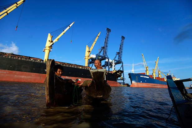 Local fishermen pass by container ships at Thilawa Port, south of Rangoon. (Photo: Reuters)