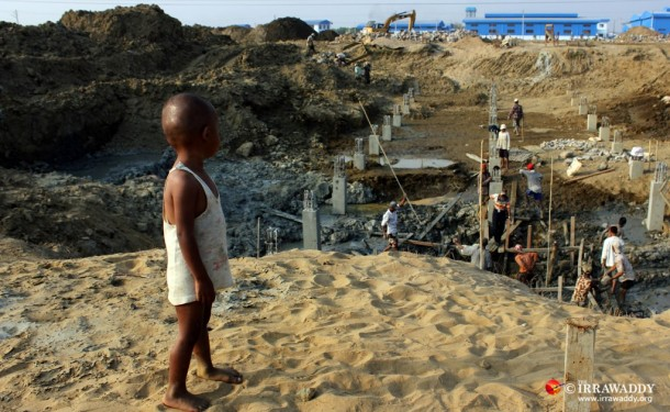A child watches as construction workers build a seaport project in Rangoon's Ahlone Township. (Photo: JPaing / The Irrawaddy)