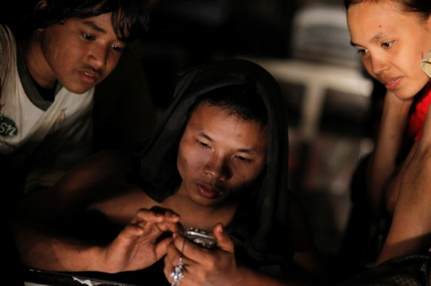Workers use their mobile phone in a vehicle on their way home in Rangoon on Jan. 18, 2013. (Photo: Reuters)