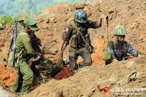 Kachin soldiers on Saturday carry the body of one of their comrades after an aerial bombardment on Thursday destroyed a bunker where four KIA soldiers had taken shelter. (Photo: Steve Tickner / The Irrawaddy)