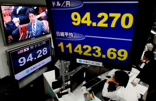 A television screen shows Japan's Prime Minister Shinzo Abe behind a monitor showing the Japanese yen's exchange rate against the US dollar and Nikkei stock average at a foreign exchange trading company in Tokyo on Feb. 12, 2013. (Photo: Reuters)
