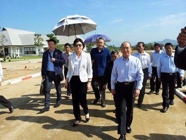President Thein Sein, front, walks ahead of Thai PM Yingluck Shinawatra (under umbrella) as the two meet in Dawei to discuss a joint development project in the area on Dec. 17, 2013. (Photo: Official Facebook page of Yingluck Shinawatra)