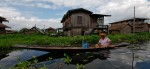 A local woman rows her boat past houses built on the water at Inle Lake. (Photo: Reuters)