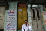 A man talks on his mobile phone by the street side of Rangoon last week. (Photo: Reuters)
