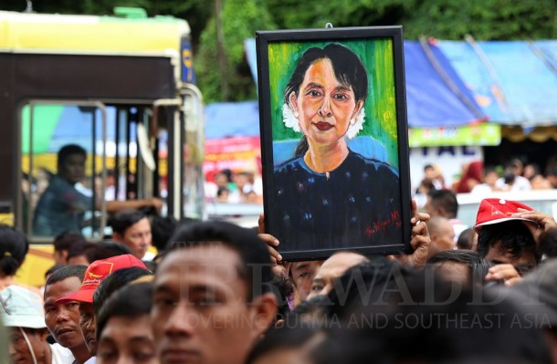 A supporter holds up a portrait of opposition leader Aung Sun Suu Kyi on June 19, 2013, at a celebration of her 68th birthday outside the National League for Democracy headquarters in Rangoon. (Photo: JPaing / The Irrawaddy)