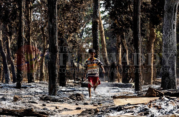 A young Muslim boy runs through the ashes of his village in Kyawe Poan Lay, Okkan township, which was razed by a Buddhist mob in May. (Photo: JPaing / The Irrawaddy)