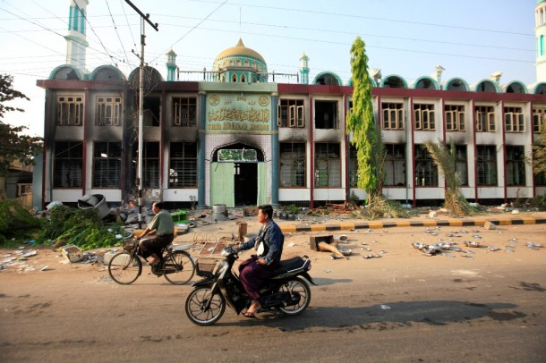 Motorcycles pass in front of a mosque that was torched during rioting in Meikhtila in March. (Photo: Reuters)