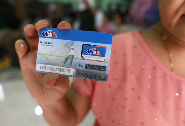A woman holds up a SIM card, which she won in a June lottery