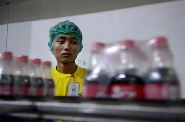 A factory worker inspects packages of Coca-Cola bottles on a conveyer belt at a new Coca-Cola plant in Rangoon in June. Coca-Cola is among big name American brands moving into Burma, but the company has not yet filed an investment report to the US Embassy. (Photo: Sean Havey / The Irrawaddy)
