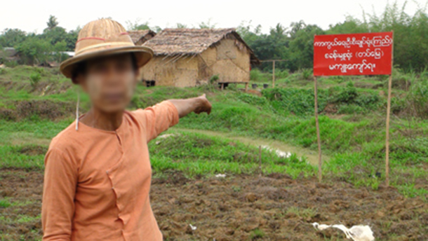 A woman points to land which, according to the sign, is now owned by the Burma Army. (Photo: The Irrawaddy)