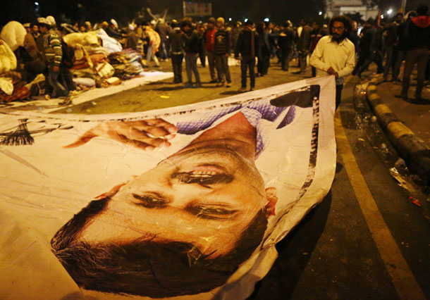 A supporter of Aam Aadmi Party removes a poster with a portrait of Delhi chief minister Arvind Kejriwal from the site of a protest after Kejriwal called off the sit-in protest on Jan. 21, 2014. (Photo: Reuters / Anindito Mukherjee)
